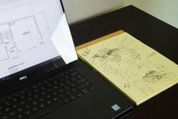 Laptop and sketchpad showing house designs